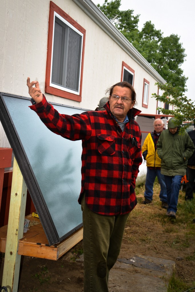Henry Red Cloud from Lakota Solar Enterprises shows a group of people how to install one of his solar air heaters at Prayer Lodge on the Northern Cheyenne Reservation on June 6, 2014.